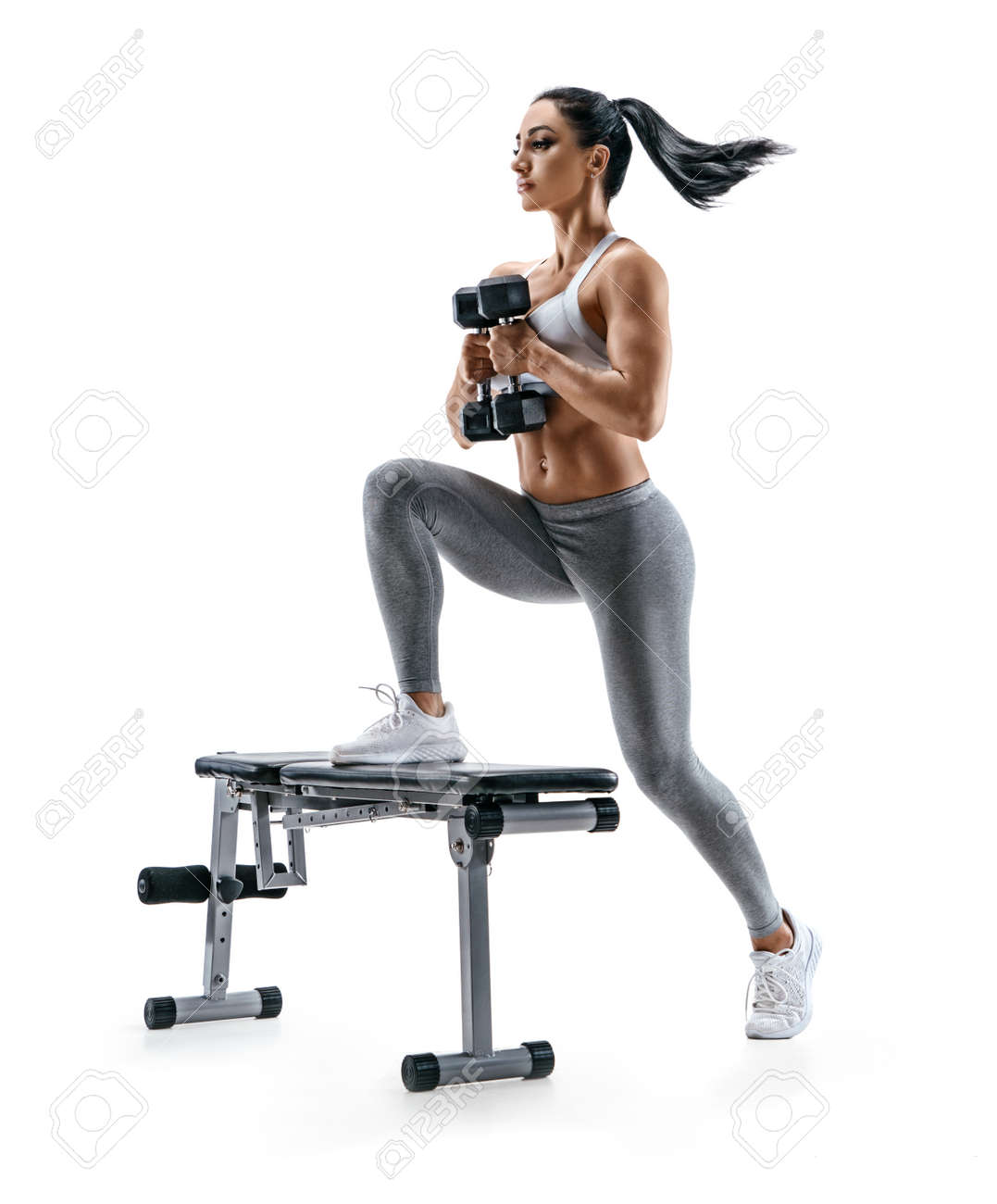 Fitness woman doing jump step ups exercise with dumbbells on bench. Photo of attractive woman in sportswear isolated on white background. Strength and motivation - 106565137