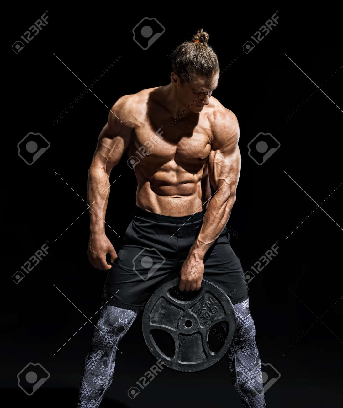 Sportive young man resting after workout with heavy weight disks. Photo of athletic man with torso and good physique on black background. Strength and motivation - 107009880