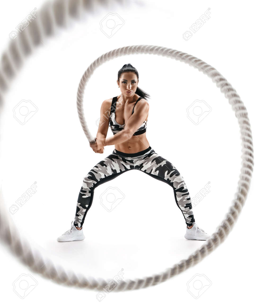 Woman doing exercises with battle rope. Photo of muscular model in military sportswear isolated on white background. Strength and motivation - 107839633