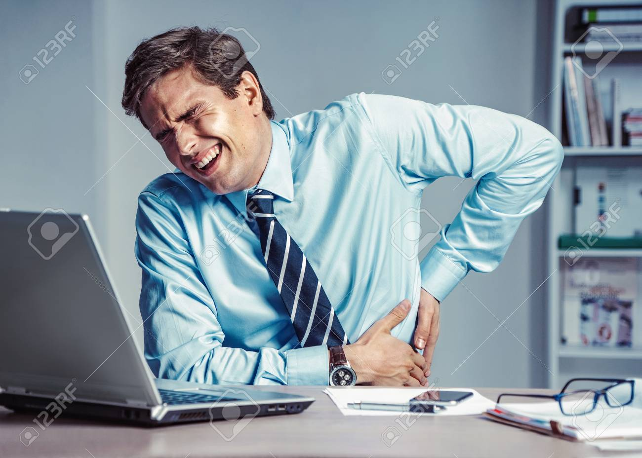 Employee suffers from severe pain in back. Photo of man working in the office. Medical concept. - 113557024