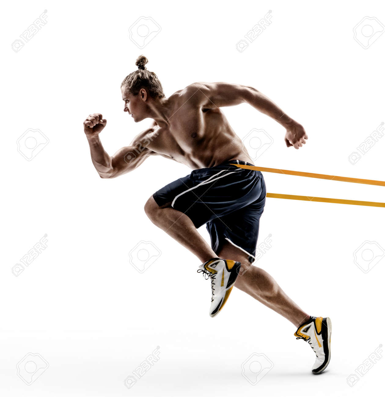 Sporty man runner in silhouette using a resistance band in his exercise routine. Photo of shirtless young man isolated on white background. Dynamic movement. Side view. Full length - 117020266
