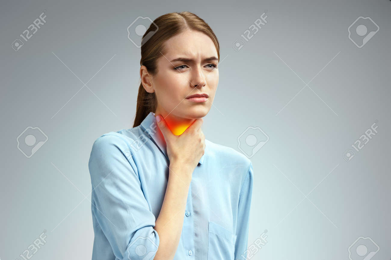 Throat pain. Woman holding her inflamed throat. Photo of american woman in blue shirt on gray background. Medical concept - 123035182