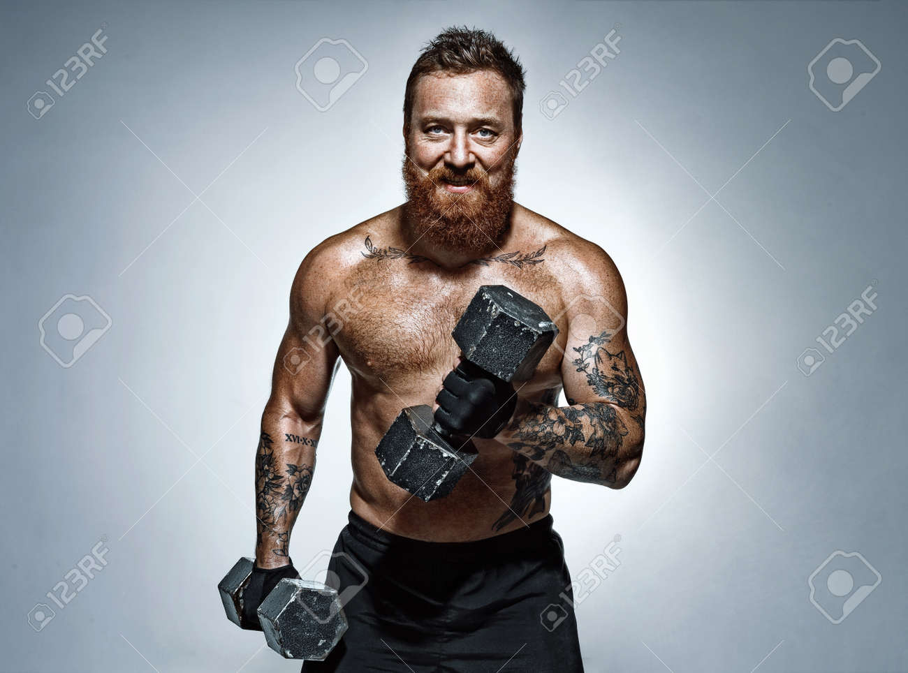 Strong man doing exercises with dumbbell. Photo of man with torso on grey background. Strength and motivation - 147130491