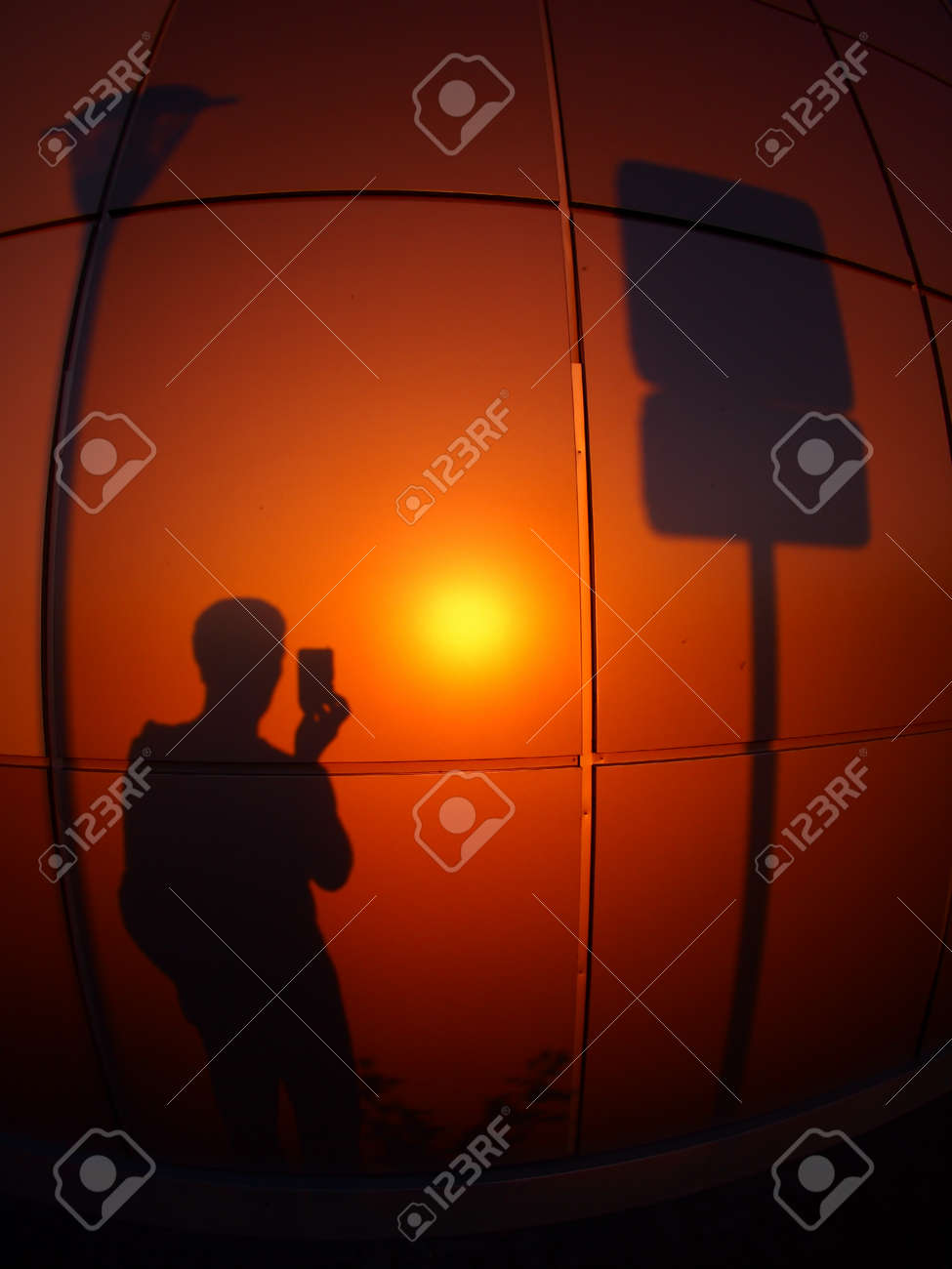 The Silhouette Of A Man On Red Orange Wall Who Photographs