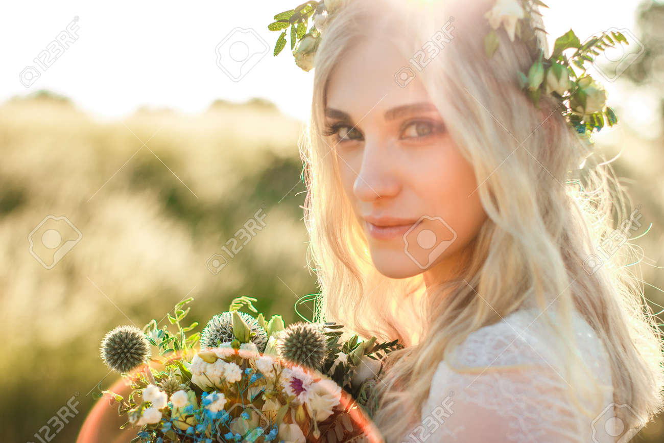 Beautiful young woman portrait in a white dress in boho style with a floral wreath in the summer in the field. Selective soft focus. - 128456264