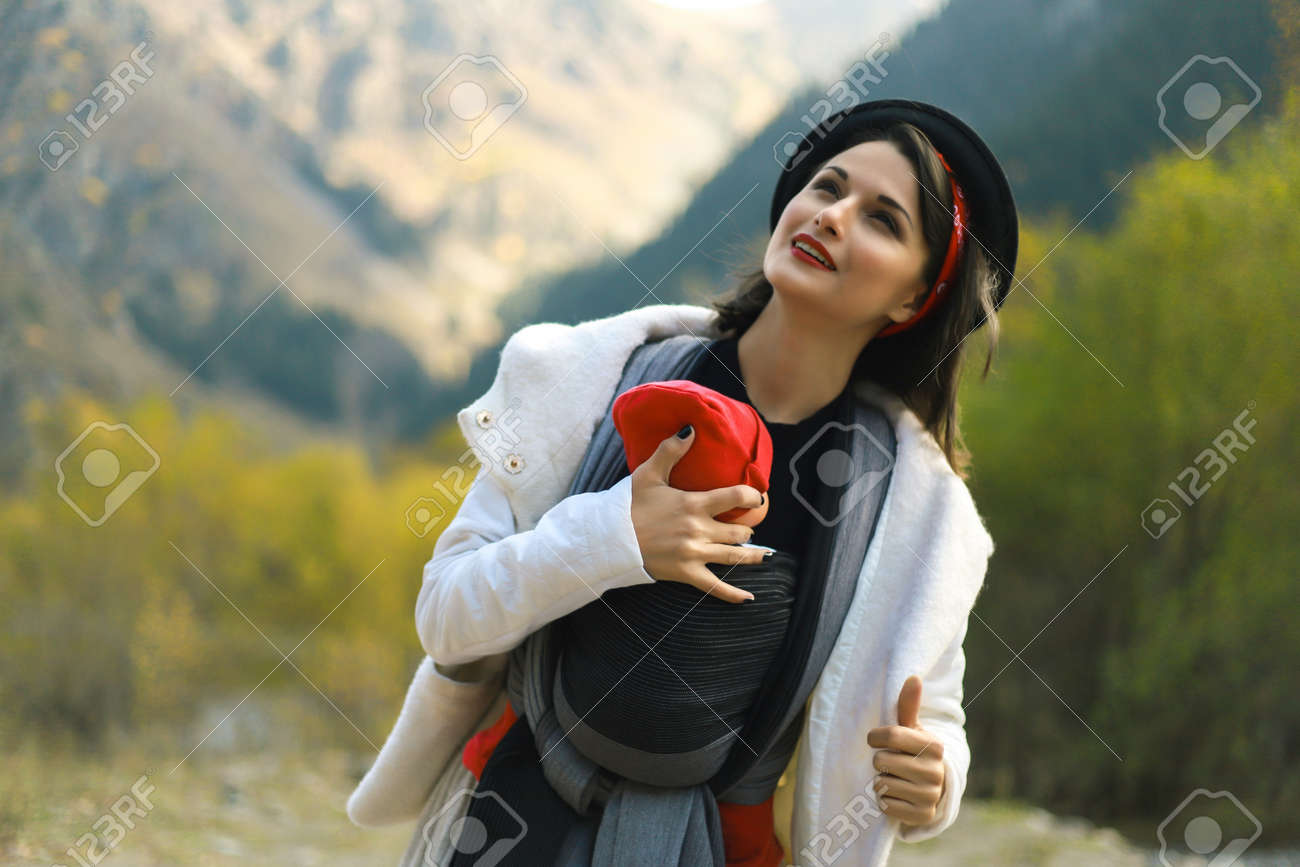 Beautiful young mother with her infant baby in sling outdoor. Woman is carrying her child and travel in autumn mountain. Babywearing concept - 154266016