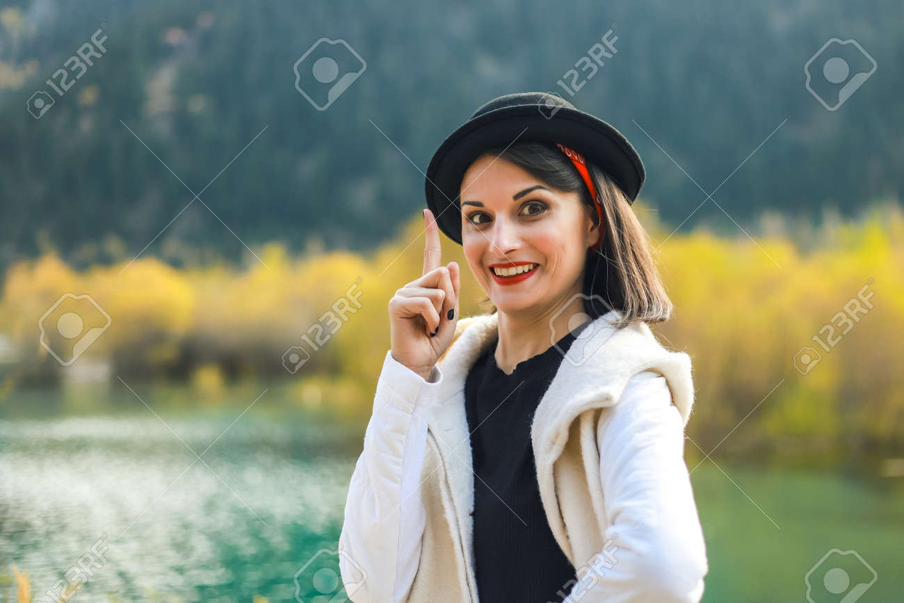 A young woman in a white coat walking in nature, look at camera, index finger up. - 166638888