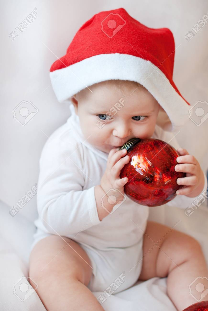 f5b763fdce7 Baby boy with red Christmas cap and balls on white background Stock Photo -  16011024
