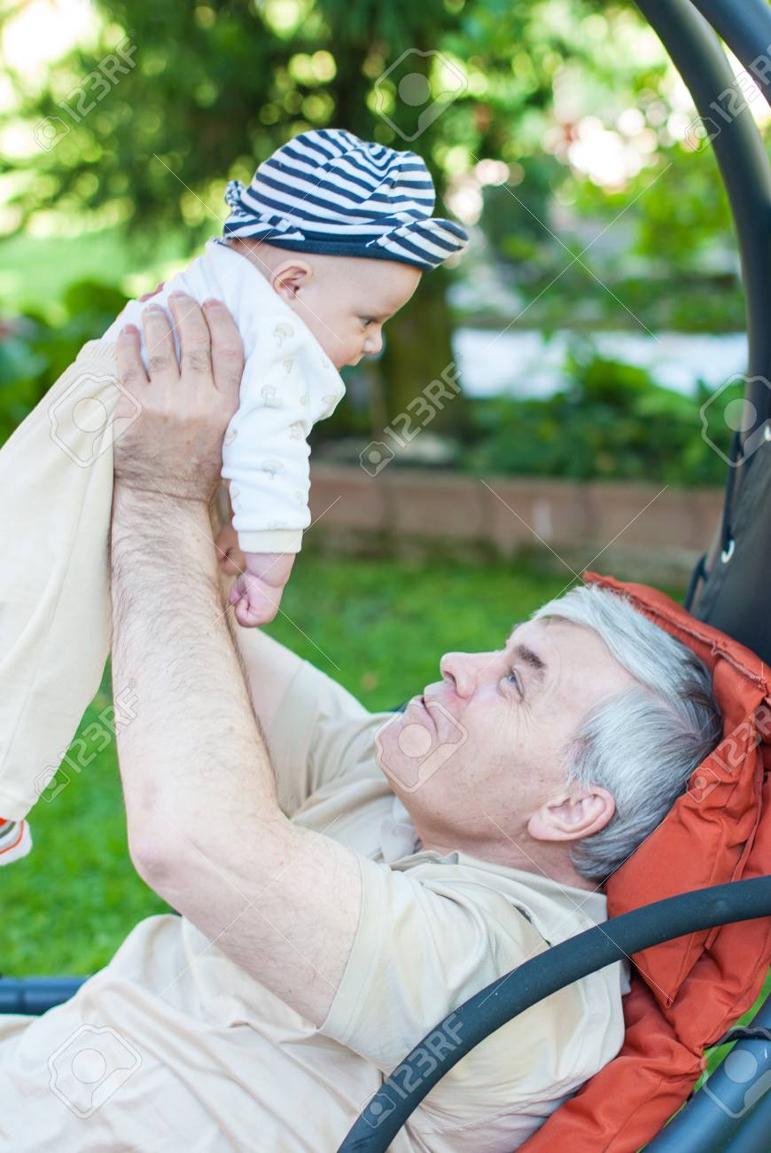 Happy grandfather and his cute grandchild baby in summer garden Stock Photo - 17341059