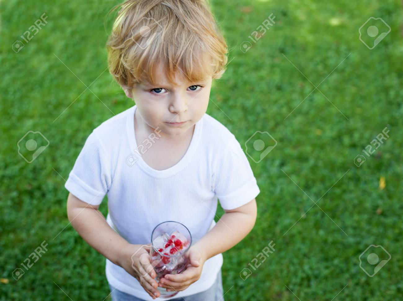 Beautiful toddler boy in summer garden with glass of berry ice cubes Stock Photo - 17213262