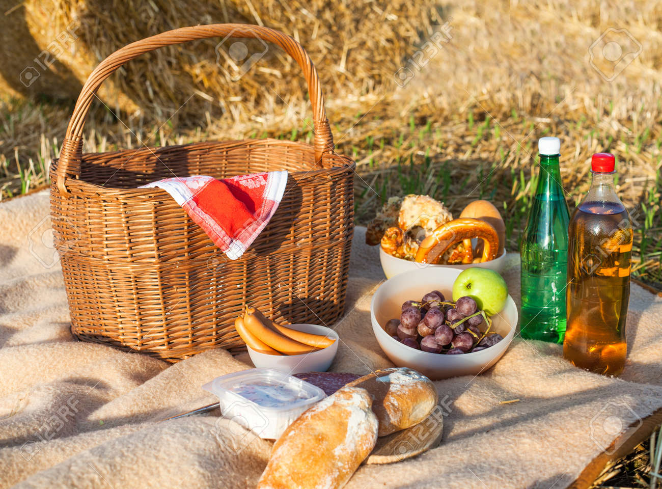 Picnic basket and different food and drinks on hay field Stock Photo - 19723501