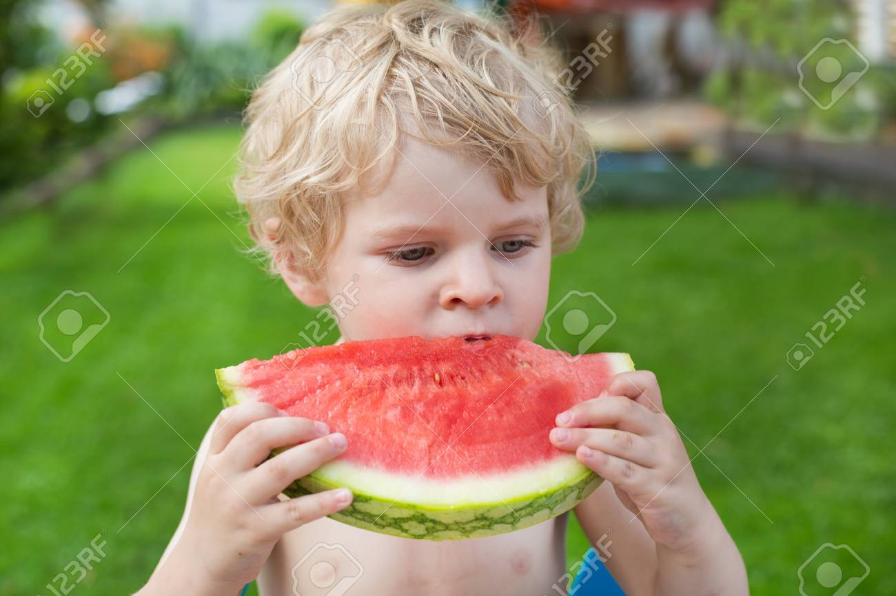 Adorable little toddler boy with blond hairs eating watermelon in summergarden Stock Photo - 20644901