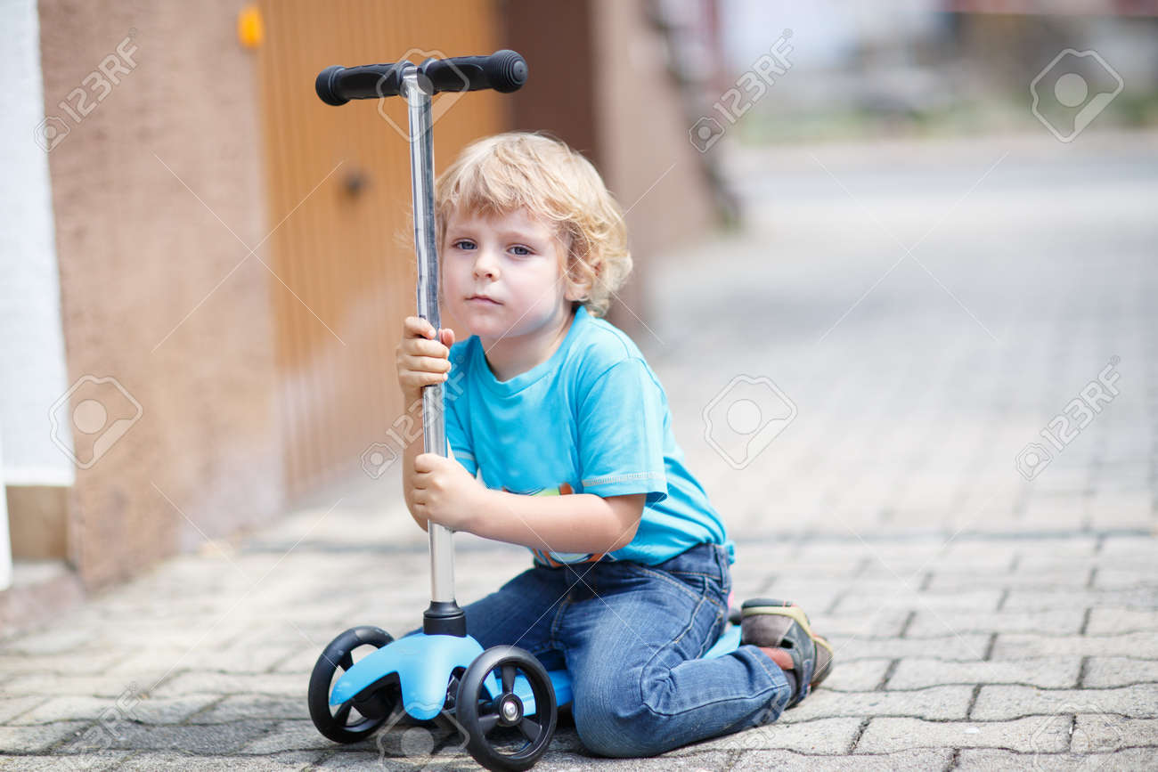 Little Toddler Boy Riding And His Scooter Bycicle In Summer Stock