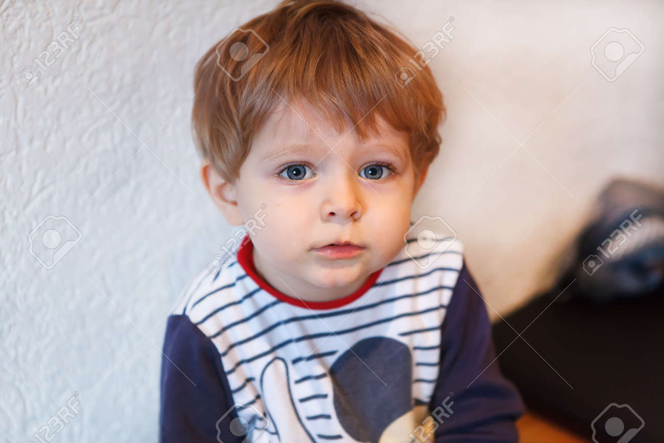 Little Toddler Boy With Blue Eyes And Blond Hair Indoor Stock Photo