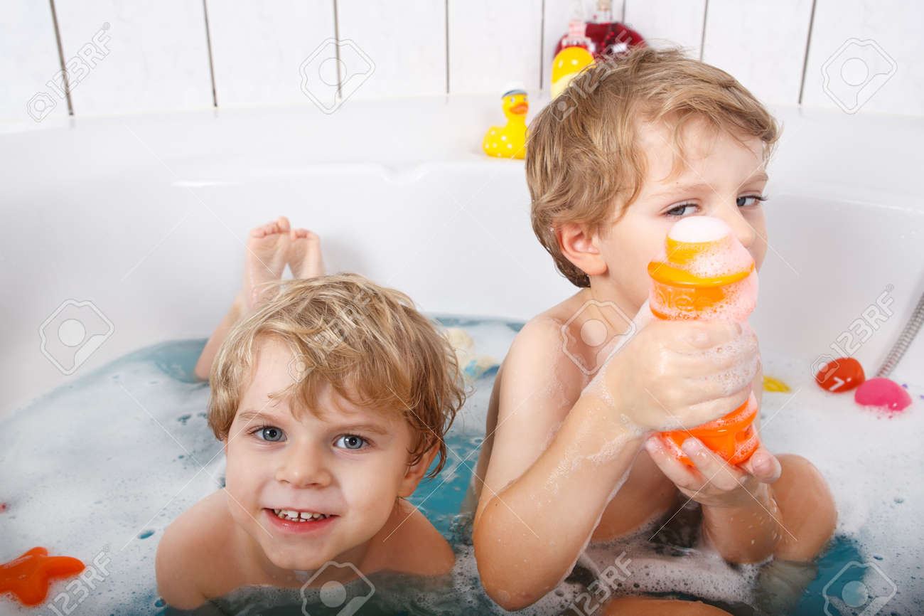 Two Adorable Little Twin Boys Having Fun With Water By Taking ...
