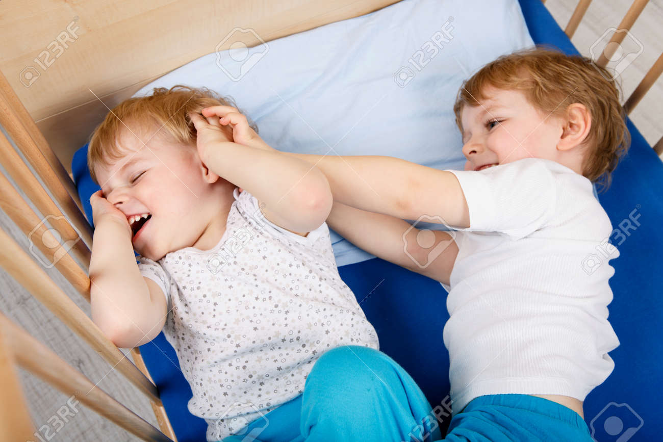 Family Of Two Little Boys Twins Having Fun Playing And Fighting In Bed At