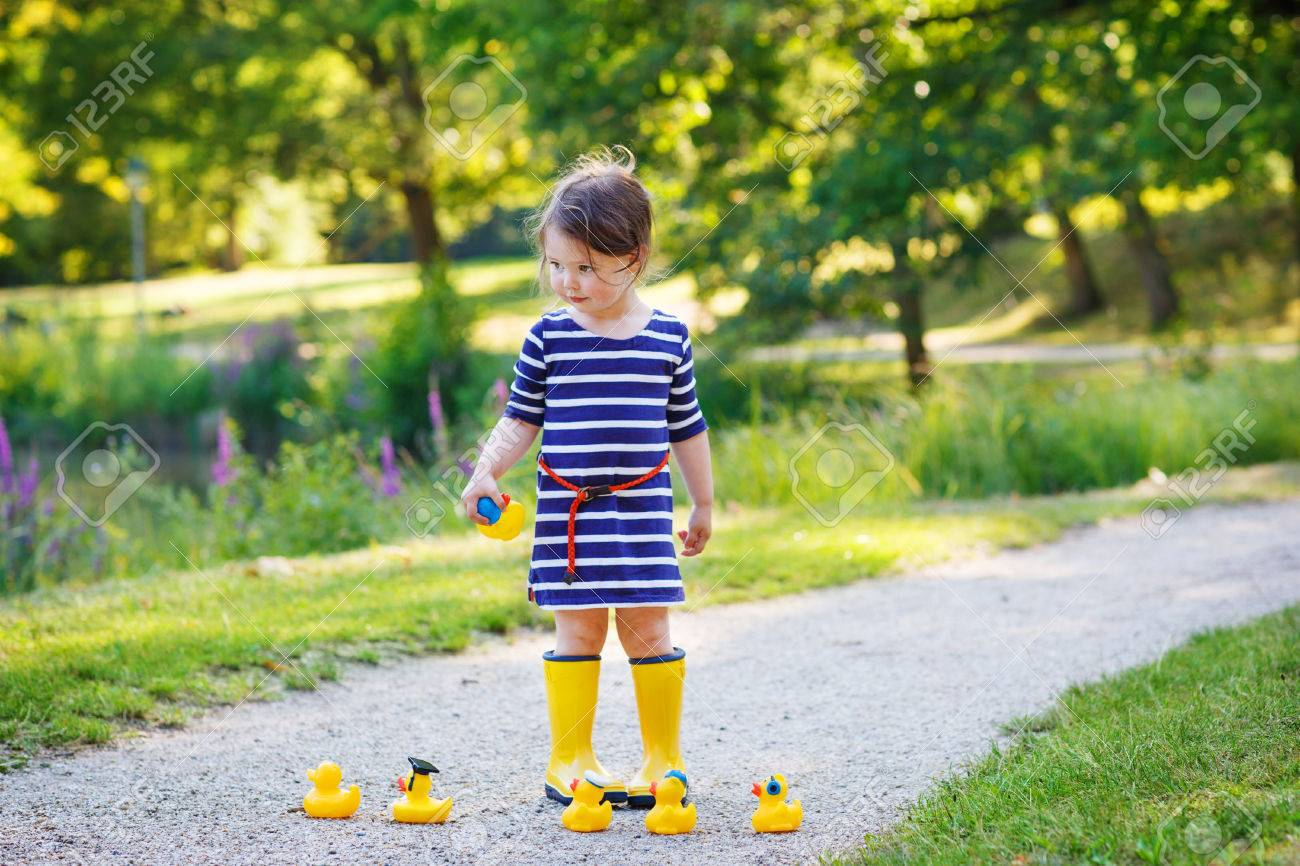 Little Girl Of 2 In Rain Boots Playing