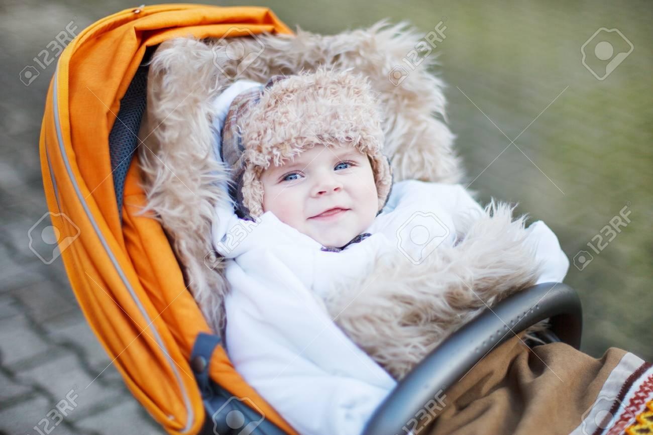 e2e20c3eb8ba Little Baby Boy In Warm Winter Clothes And Orange Pram Outdoor Stock ...
