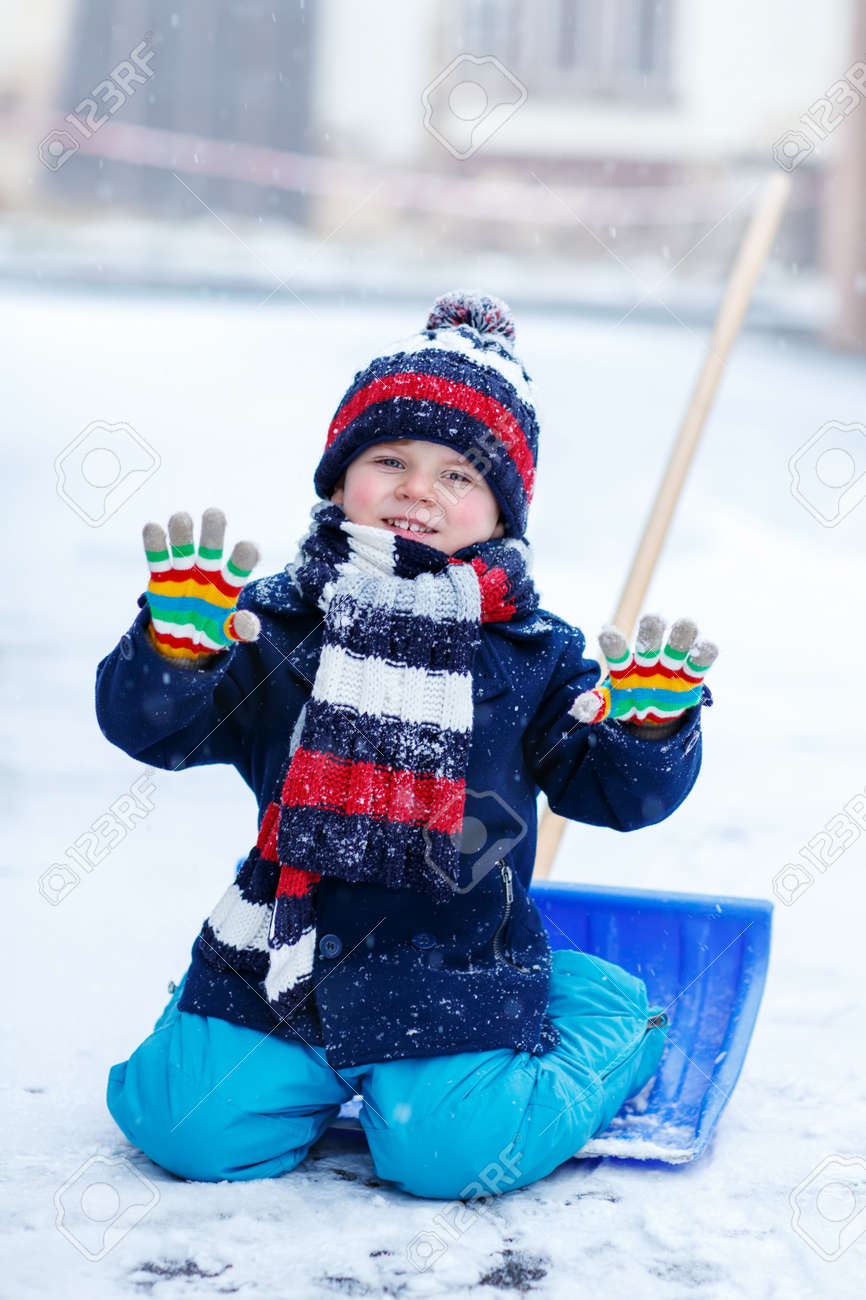 d835af45768 Cute little funny boy in colorful winter clothes having fun with snow  shovel