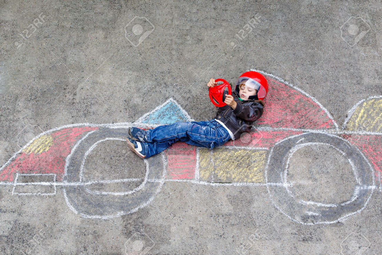 funny kid boy having fun with race car picture drawing with