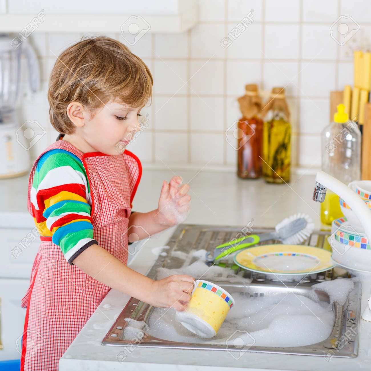 Funny Blond Kid Boy Washing Dishes In Domestic Kitchen. Child ...