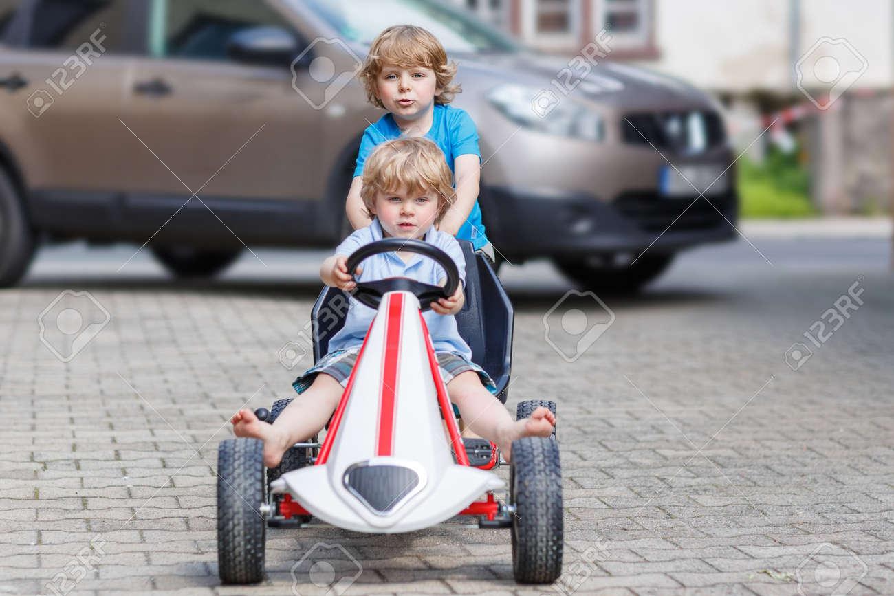 two happy little boy friends having fun with toy race car in