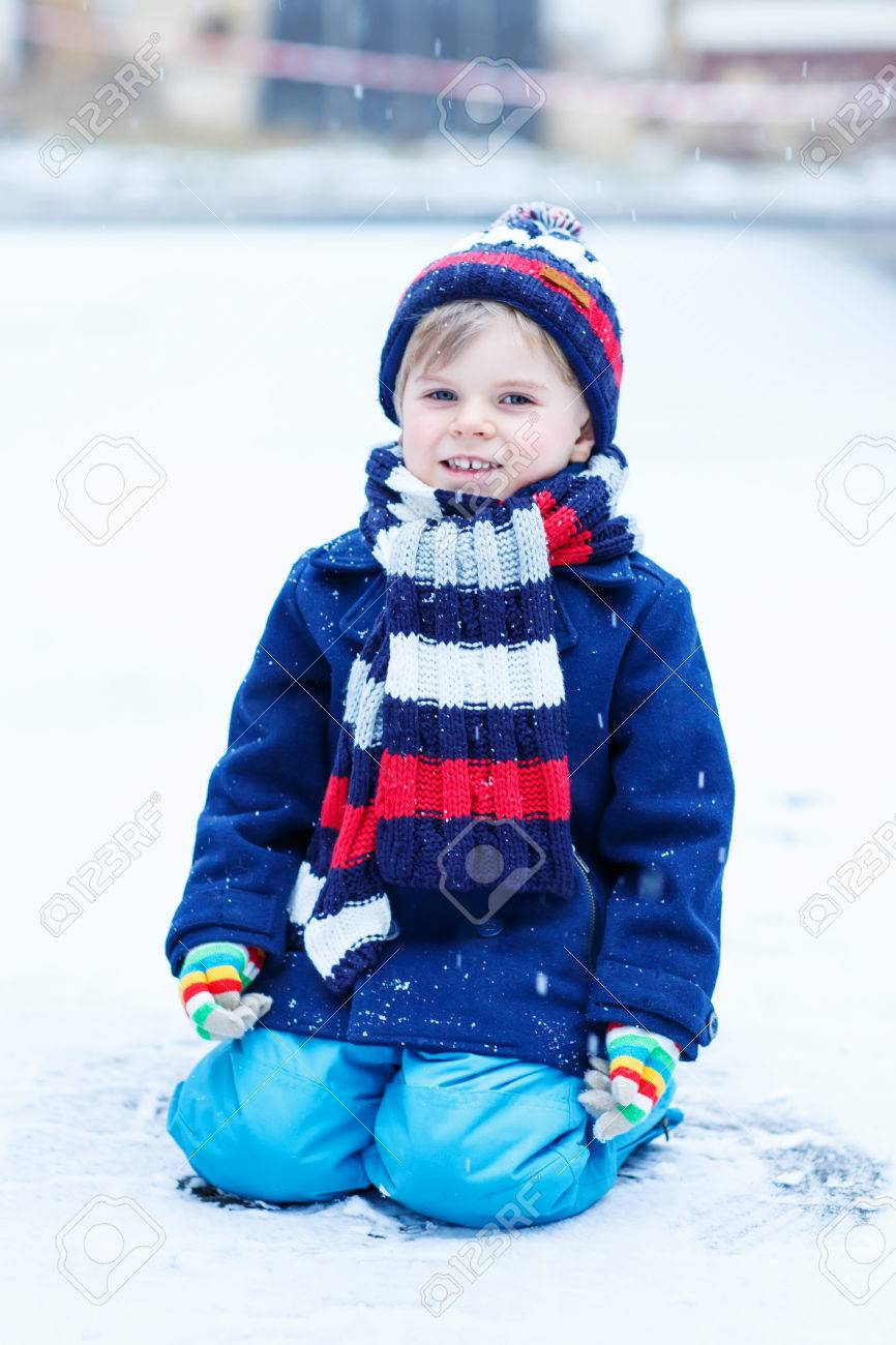 6486a1a3b Cute Little Funny Kid Boy In Colorful Winter Clothes Sitting.. Stock ...