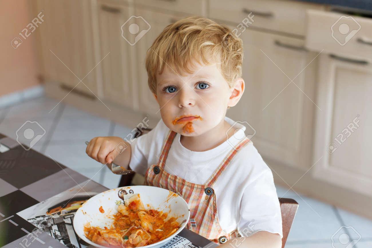 Reizende kleine junge 2 jahre essen pasta innen. kleinkind kind in ...