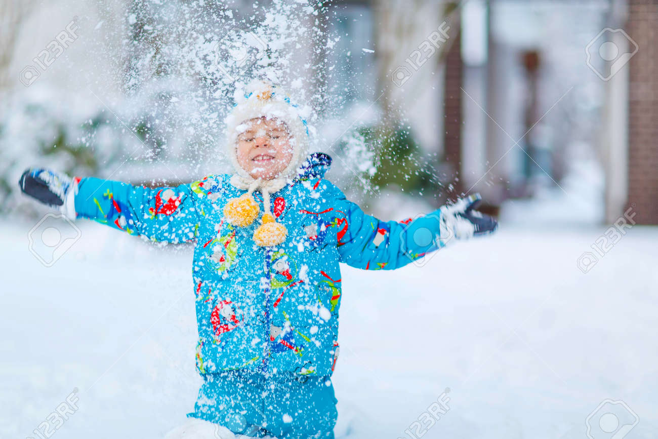 Cute little funny boy in colorful winter clothes catching snow and  snowflakes 42b020568