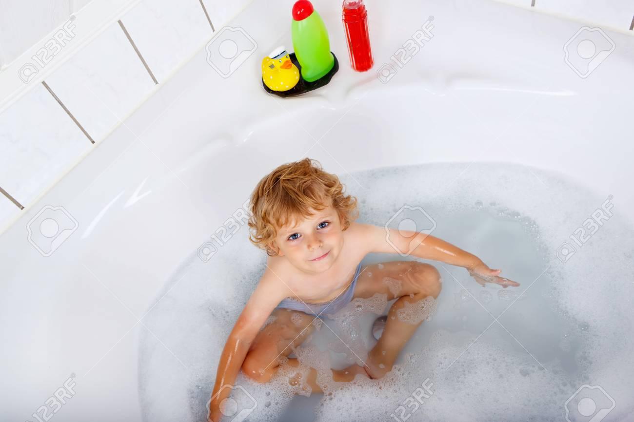 Vasca Da Bagno Bambini : Ragazzo biondo sveglio del bambino che gioca e nuota prendendo il