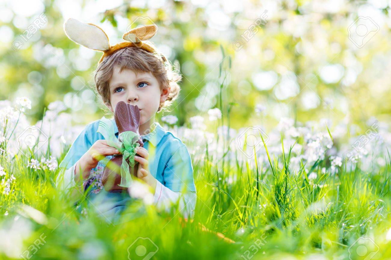 cute little kid boy with easter bunny ears celebrating traditional