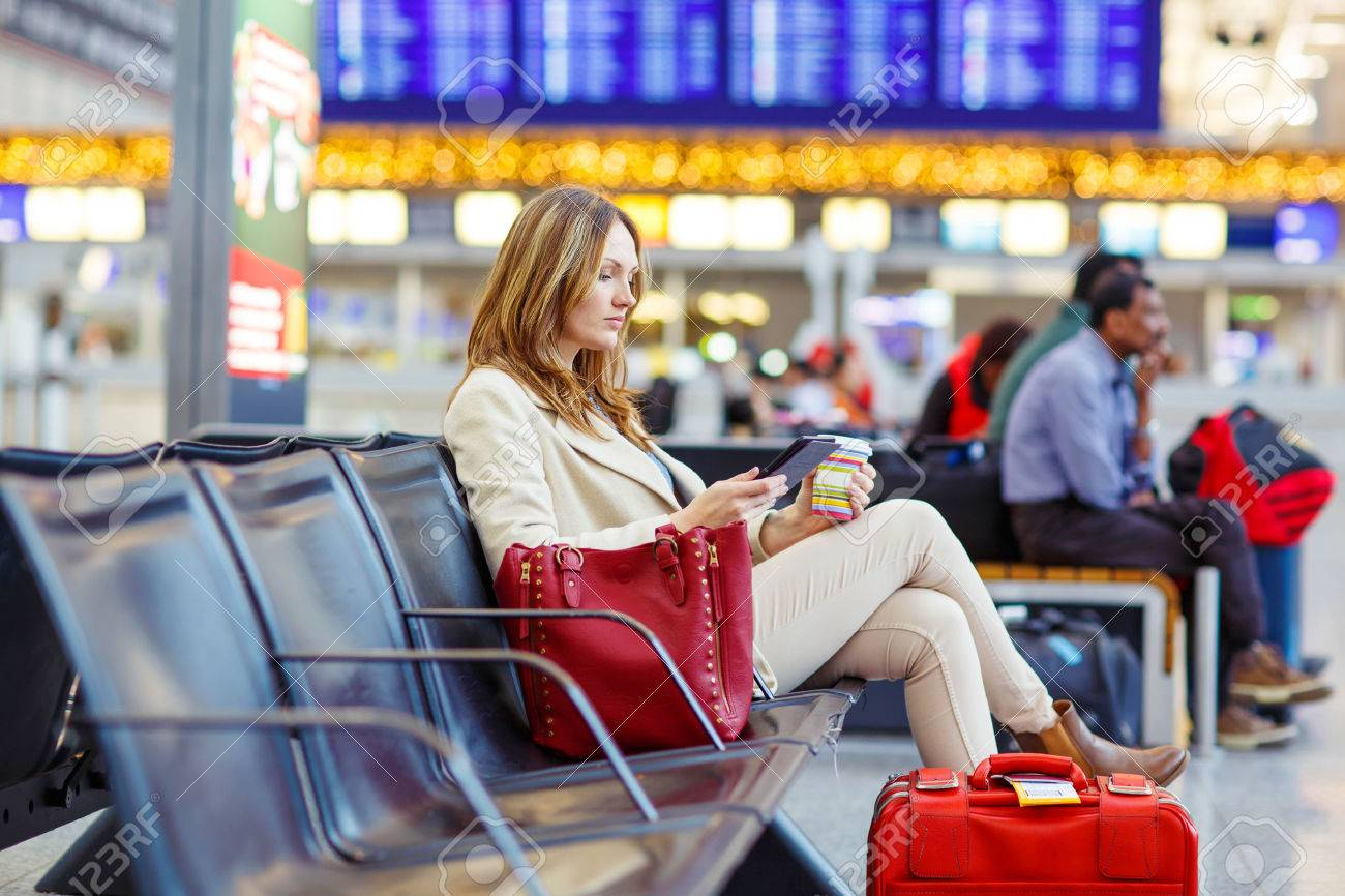 Business woman at international airport reading book and drinking coffee in terminal. Angry passenger waiting. Canceled flight due to pilot strike. - 54790605