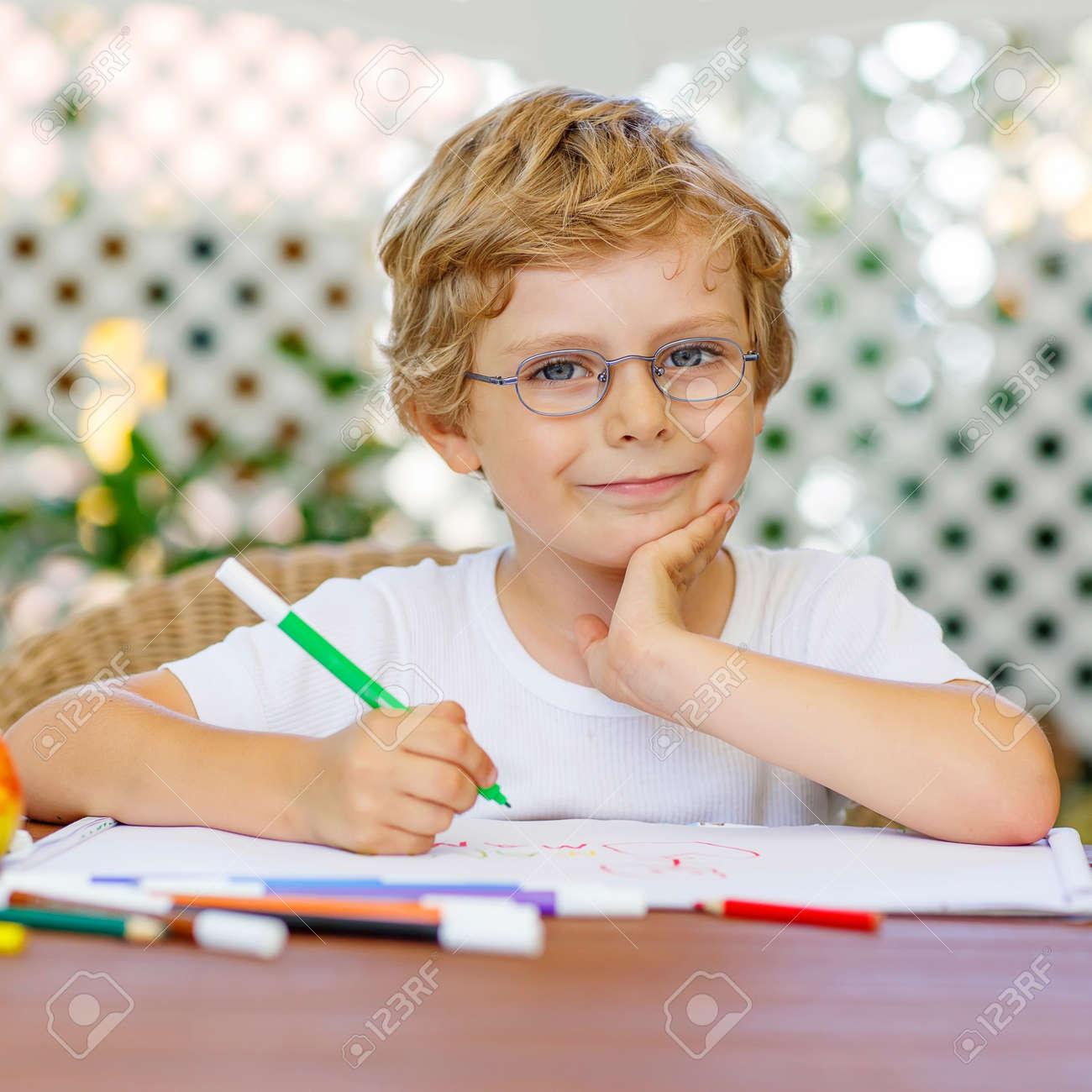 ce17c560c09 Portrait of cute happy preschool kid boy with glasses at home making  homework. Little child