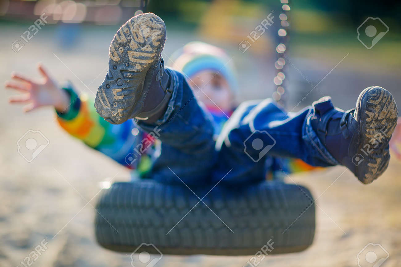 Funny kid boy having fun with chain swing on outdoor playground. child swinging on warm sunny spring or autumn day. Active leisure with kids. Selective focus - 54764490