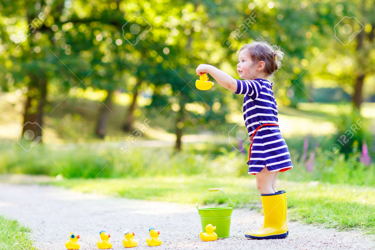 f54af602a Adorable Little Kid Girl Playing In Forest Playground With Yellow ...
