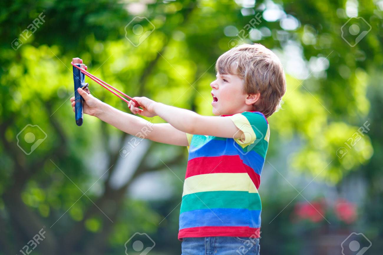 Funny little kid boy shooting wooden slingshot against green tree background child having fun in