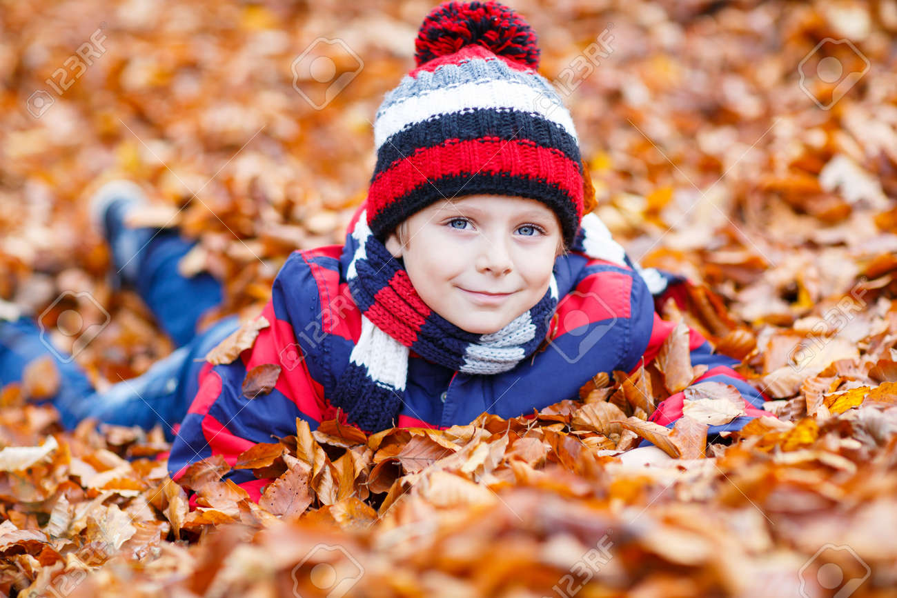 55981b54c22 ... day. With hat and scarf. Portrait of happy cute little kid boy with  autumn leaves background in colorful clothing. Funny