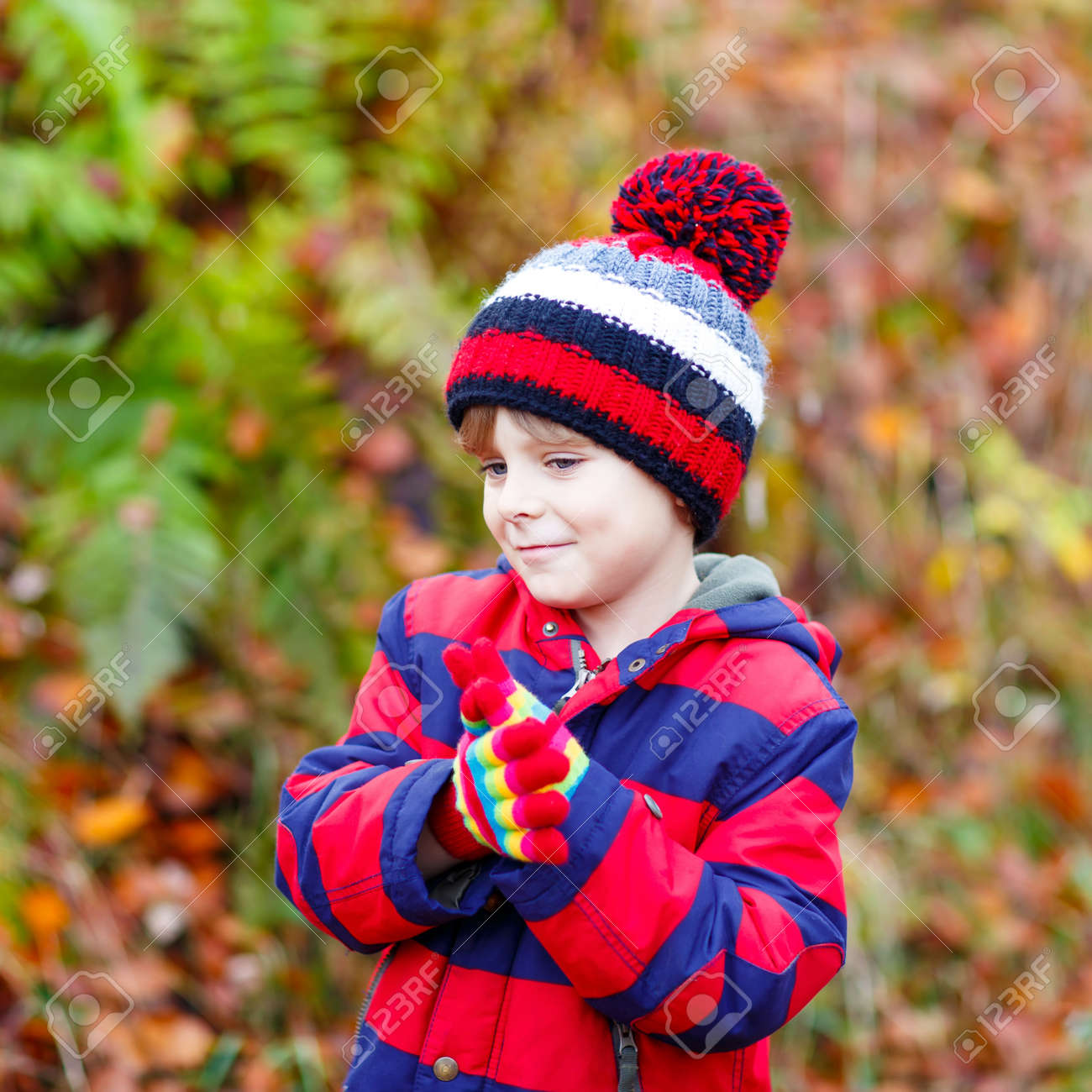 8d3af003e36 ... day. With hat and gloves. Portrait of happy cute little kid boy with  autumn leaves background in colorful clothing. Funny