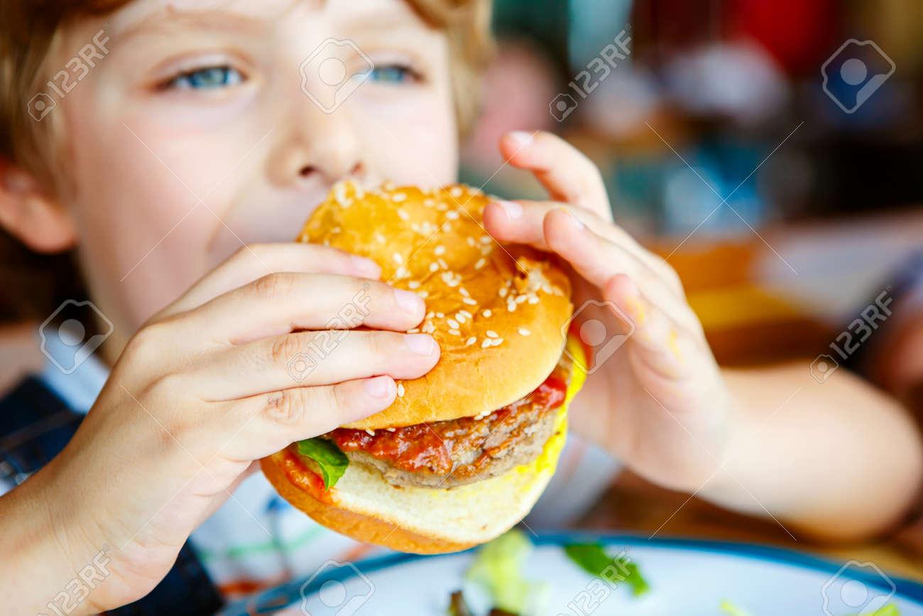 Cute Healthy Preschool Kid Boy Eats Hamburger Sitting In Cafe