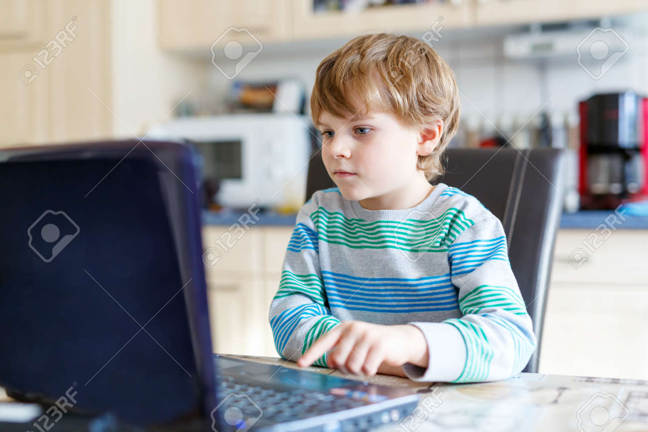 Kid Boy Surfing Internet And Playing On Computer