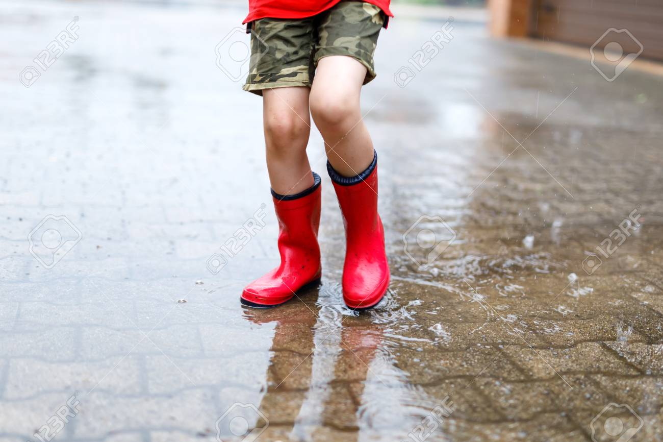 c53f3329340 Child wearing red rain boots jumping into a puddle.