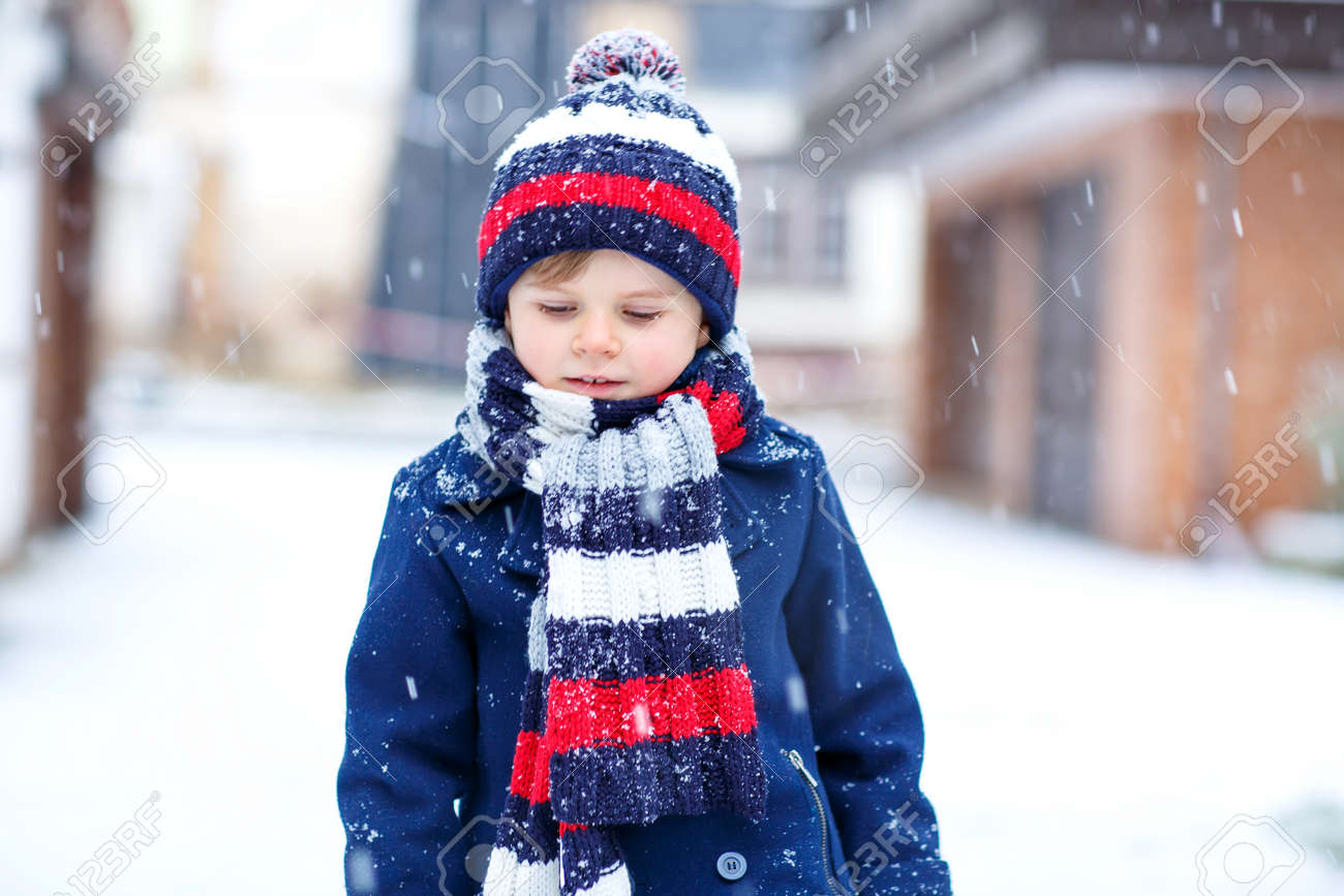 Cute little funny kid boy in colorful winter fashion clothes having fun and  playing with snow 00436bebb