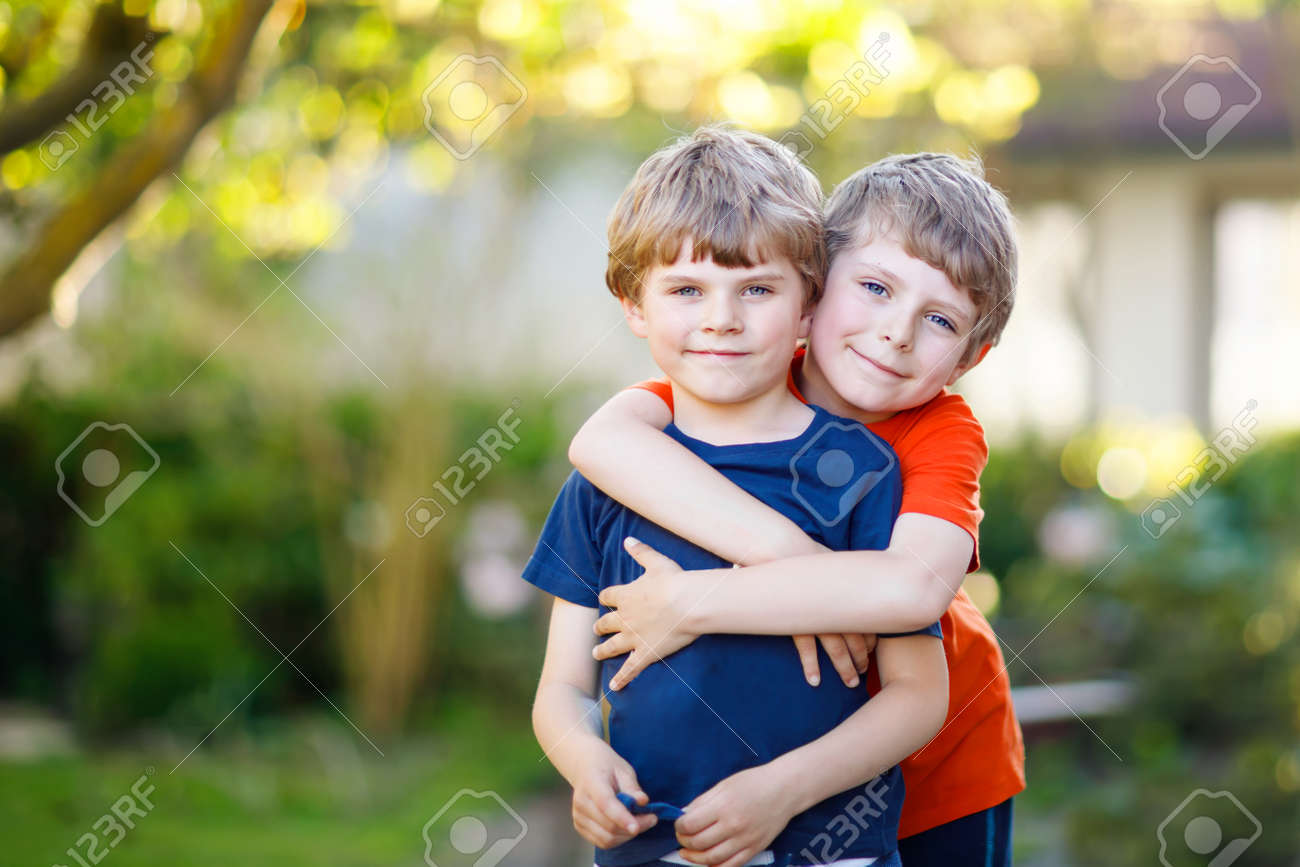 two little active school kids boys twins and siblings hugging