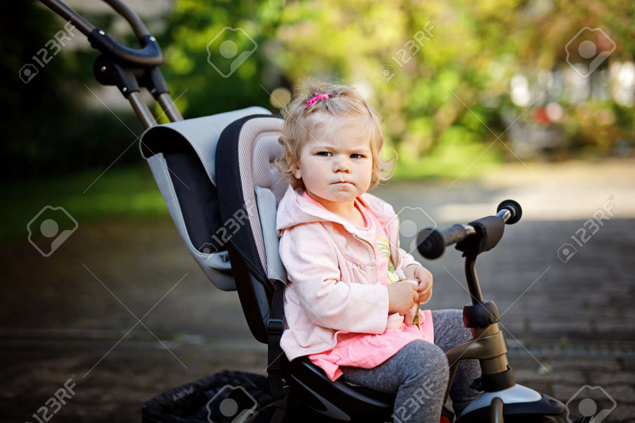 78e52b4539c Cute adorable toddler girl sitting on pushing bicyle or tricycle. Little  baby child going for