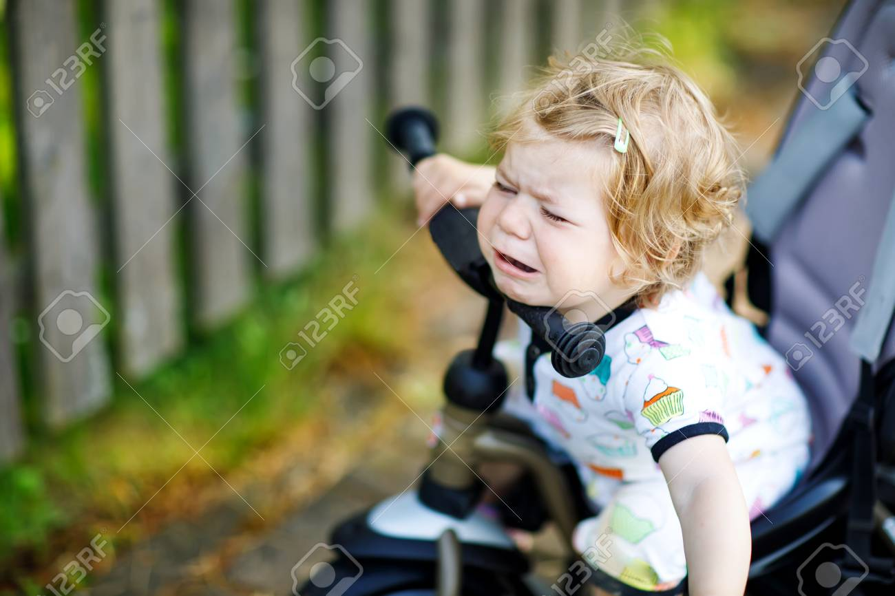66162c7ccf2 Cute adorable crying sad toddler girl sitting on pushing bicyle or tricycle.  Little baby child