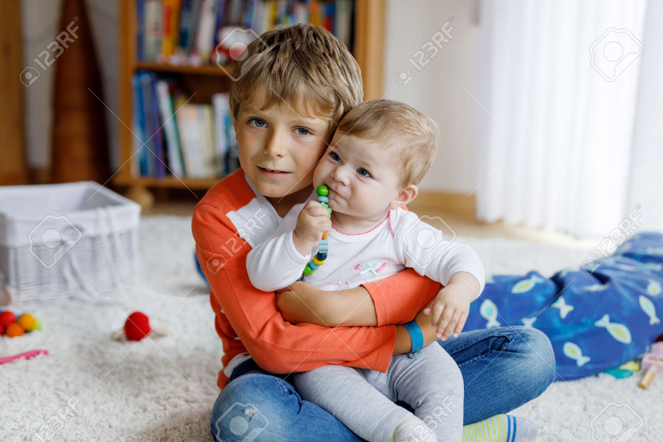 Happy little kid boy with newborn baby girl cute sister siblings brother and