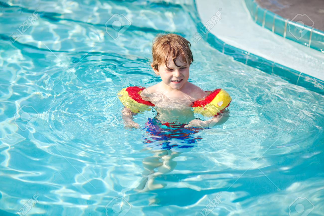 Happy little kid boy having fun in an swimming pool. Active happy..