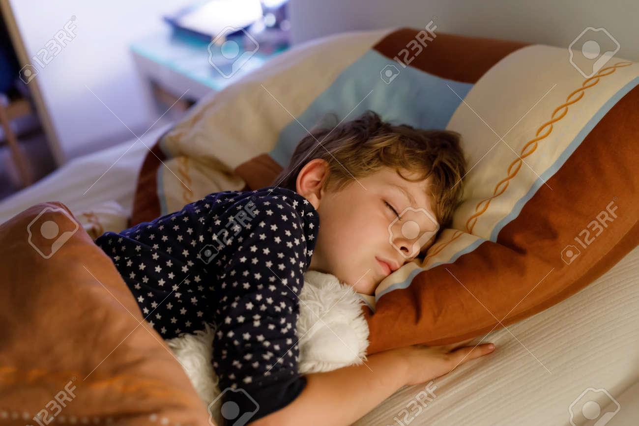 Little Preschool Kid Boy Sleeping In Bed With Colorful Lamp