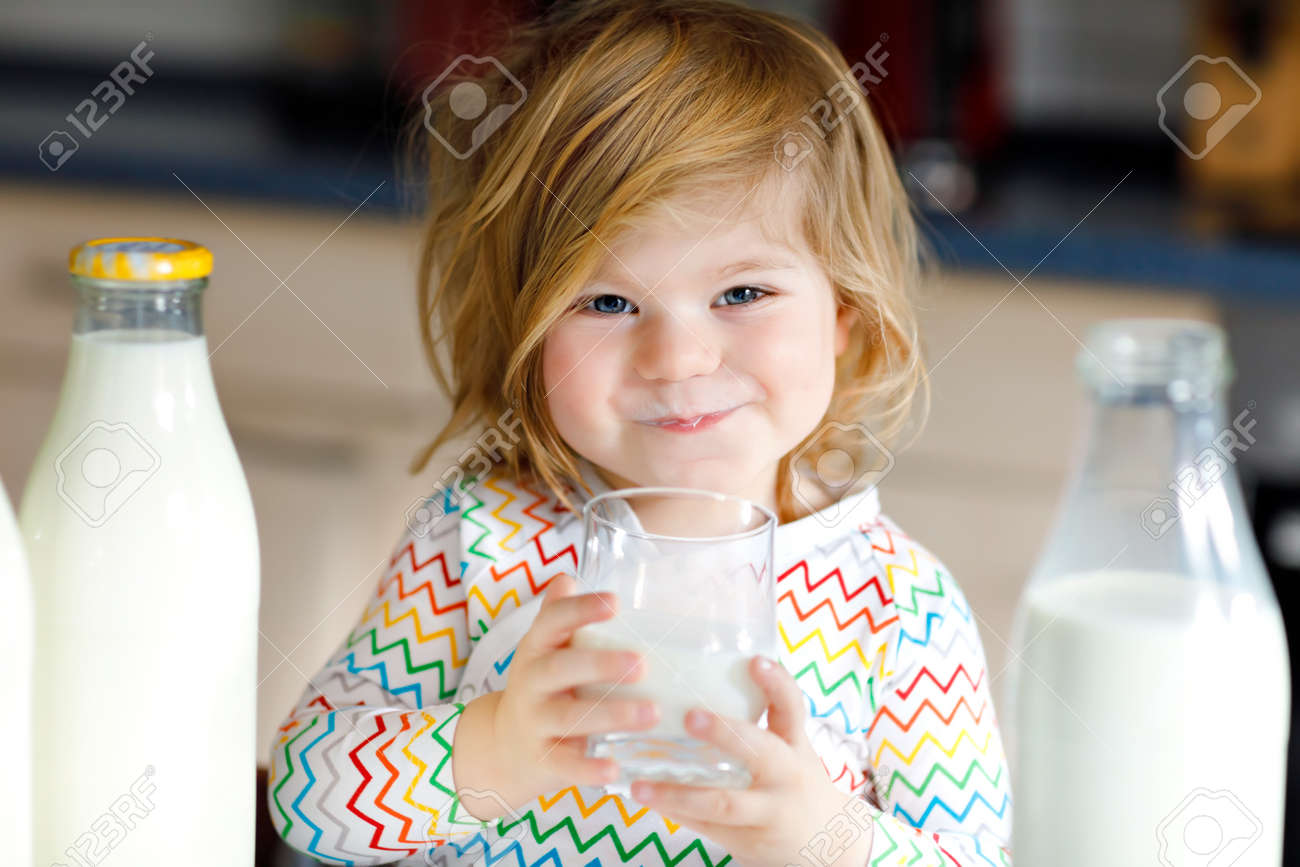 Adorable toddler girl drinking cow milk for breakfast. Cute baby daughter with lots of bottles. Healthy child having milk as health calcium source. Kid at home or nursery in the morning. - 119615839