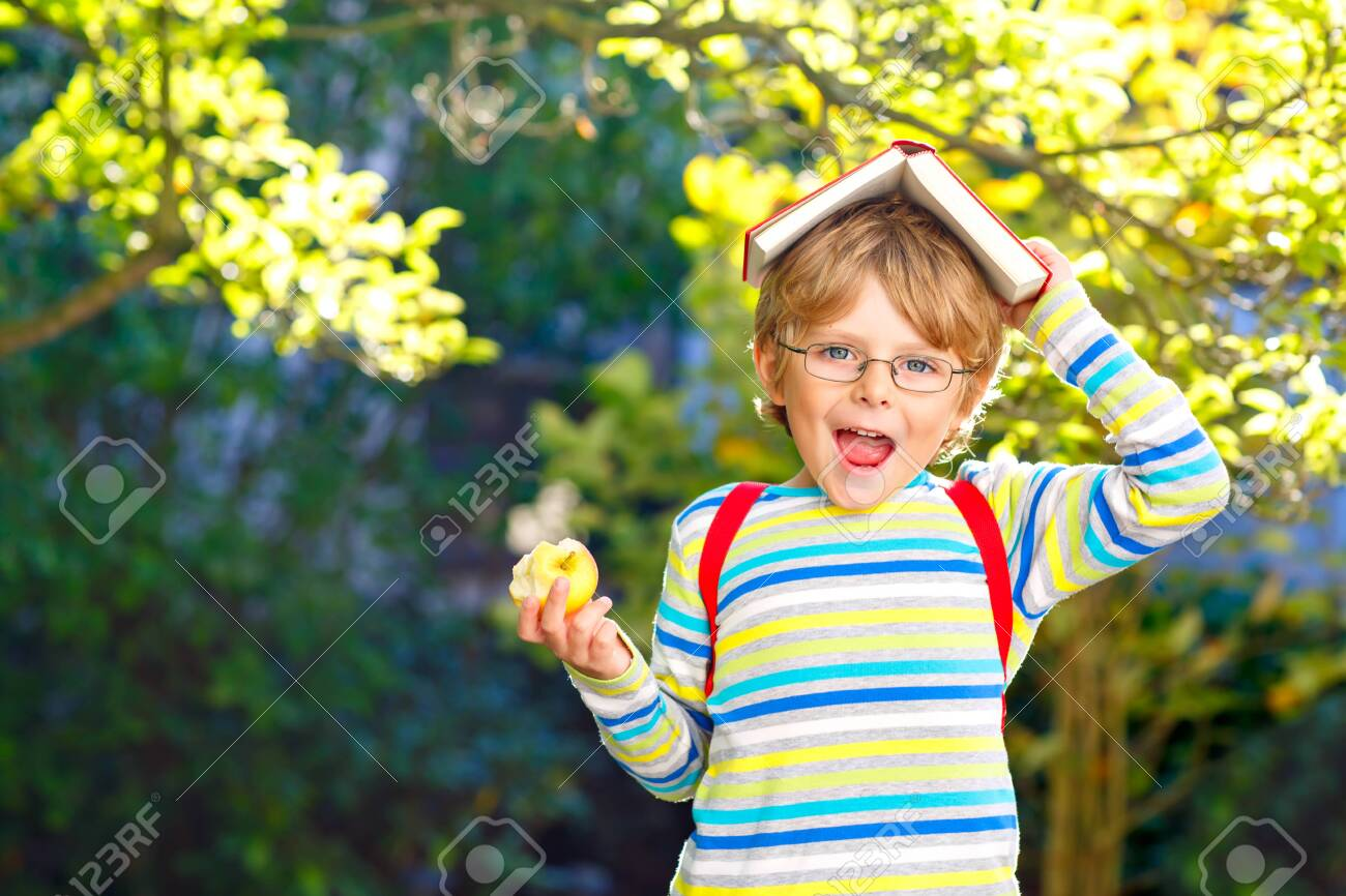 Happy little preschool kid boy with glasses, books, apple and backpack on his first day to school or nursery. Funny healthy child outdoors on warm sunny day, Back to school concept. Laughing boy. - 124136099